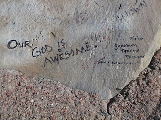 Beautiful Our god is awesome god written on rock sand in mountain picture