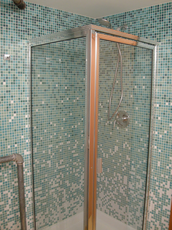 For this corner shower, I tiled two walls then built-out the clear  title=