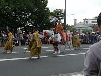 銅像・高山彦九郎を前に進む行列