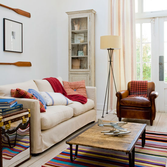 Nautical-Living-room-with-colorful-striped-carpet-low-level-wooden-table-cosy-sofa-wooden-floor-and-decorations