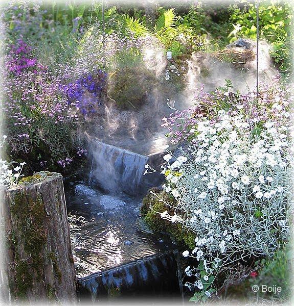 Bäcken med vattenfall och dimma