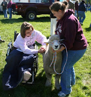 Kaitlyn Fuss (Frederick County) examines the fleece of a Romney ewe held by UMES student Shannon Uzelac