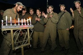 Servicemen in the Israel Defense Force (IDF) engage in an intimate celebration of Hanukkah as they light the first candle of the menorah. (Creative Commons/Google Images)