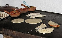 A color photo of a large cast iron comal or griddle.