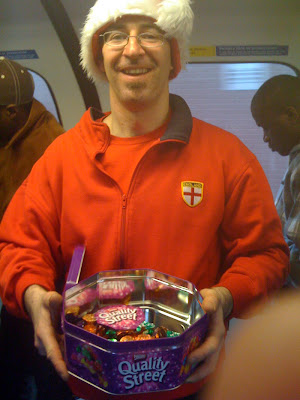 Central Line Tube Santa giving away Quality Street sweets