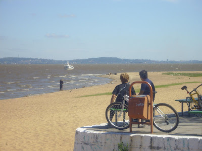 foto de um casal admirando o estuário Guaíba em um dia ensolarado, com o barco Travessia ancorado no bairro Ipanema em Porto Alegre