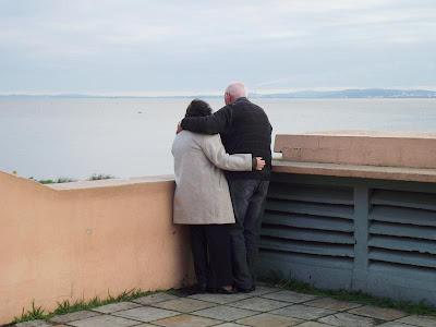 foto de um casal de idosos abraçados admirando o lago Guaíba, na usina do gazômetro, em um dia nublado em porto alegre