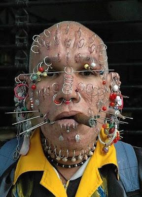 Homem com piercings pelo rosto todo