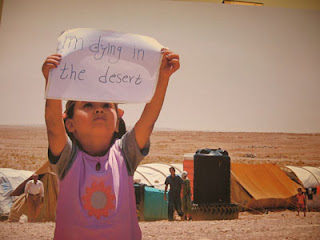 'I'm dying in the desert' - A Palestinian Iraqi refugee, in a camp on the Syrian border, holds up a sign she made herself. [UNHCR photo 7/25/07]
