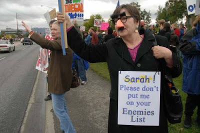 Masked protester with sign at anti-Palin rally in Anchorage - 'Sarah, please don't put me on your enemies list'.