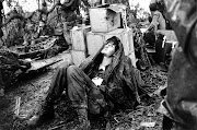 A wounded U.S. paratrooper grimaces in pain while waiting for medical .
