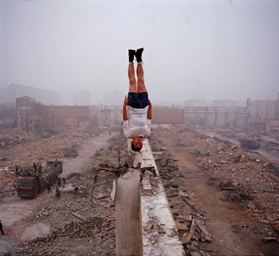 Lei Wei photo, man upside down on the top of a wall in the middle of ruins