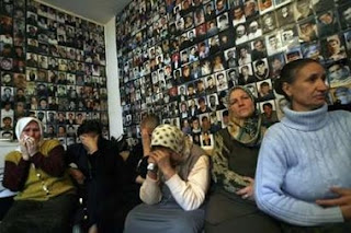 Women from Srebrenica react to television coverage from The International Court of Justice in front of a wall covered with pictures of their missing loved ones in an office in Tuzla February 26, 2007.