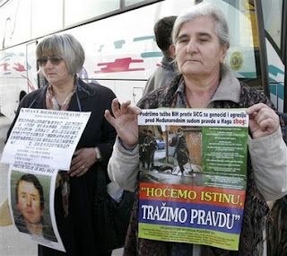 Relatives of Srebrenica victims hold posters relating to the massacre as they prepare to leave Sarajevo in Bosnia early Saturday, Feb. 24, 2007 for the Netherlands to attend Monday's verdict by the International Court of Justice in a genocide case against Serbia and Montenegro in the Hague.