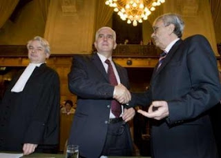 Bosnian agent Sakib Softic (C) shakes hands with Head of the Law Council of the Ministry of Foreign Affairs of Serbia and Montenegro Radoslav Stojanovic (R) while Dutch Attorney for Bosnia Phon van den Biesen looks on at the International Court of Justice in the Hague February 26, 2007. The top U.N. court ruled on Monday that Serbia did not commit genocide through the killing that ravaged Bosnia during the 1992-95 war, but said Serbia had failed in its obligation to prevent and punish genocide.
