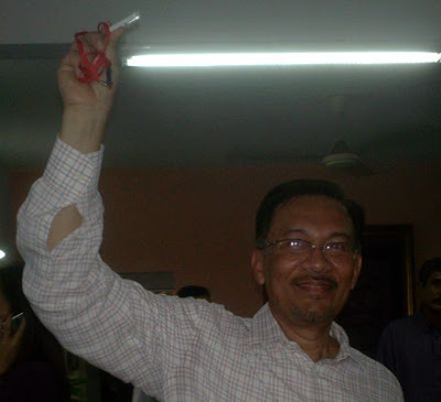 nwar Ibrahim holding the thumb drive containing the VK Lingam tape