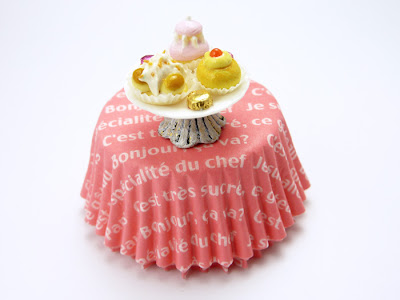 Miniature cake stand holding a selection of miniature handmade pastries shown on a full size paper cake case