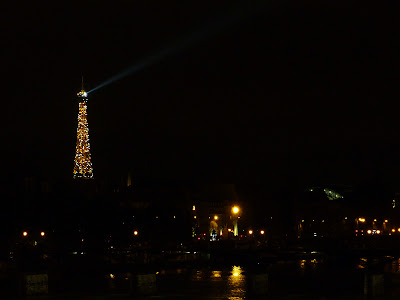 The Eiffel Tower at night seen from the Pont Neuf bridge