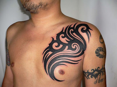 Man with drawing of tribal tattoo design on his shoulder, sleeve,