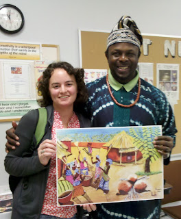 myself and Ibiyinka Alao holding a print of one of his paintings