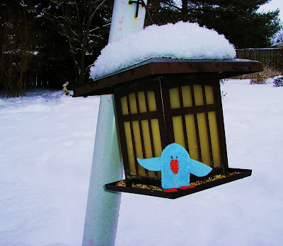 A photograph of one of my bluebird finger puppet crafts sitting on a bird feeder in the backyard