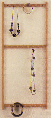 wall-mounted wood necklace rack with jewelry hanging on it