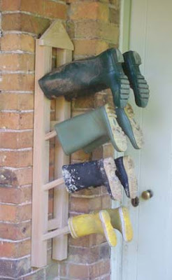hanging (wall-mounted) boot rack with 4 pairs of boots on it