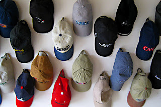 baseball caps hanging on a wall