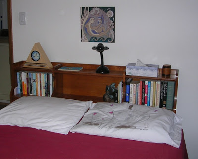 bookcase headboard with books, lamp, clock, etc.