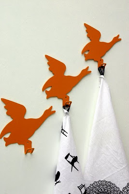 3 orange flying duck hooks, two holding towels