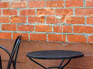 metal furniture in front of brick wall (c)David Ocker