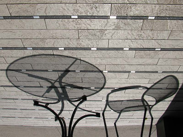 Shadows of table and chair at a Starbucks patio where they play no music