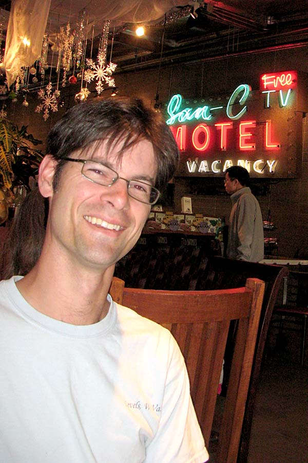guitarist and Pomona college professor Joti Rockwell at a coffee shop with an unexpected neon sign