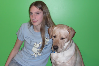 Toby still looks the same in this picture, I'm wearing my cute blue Southeastern Guide Dog shirt, it has 2 cute little puppies that made pawprints on the shirt, and are trying to climb into my pretend pocket, the green wall is the background