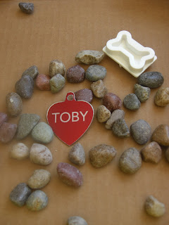 Picture of the things I was going to put on the stone - Toby's red name tag, some small rocks and the dog bone stamp
