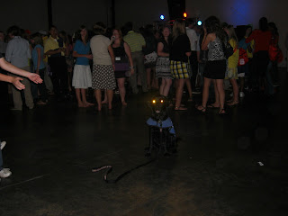 Photo of Sparkie in a sit-stay in the middle of the dance floor - his eyes are glowing, and their is a huge crowd of people behind him