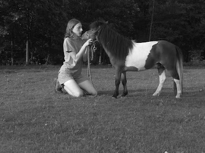 Black/white picture of me on my knees blowing a kiss  to Flash - a brown/white paint horse (while on my knees - he still isn't taller than me!)