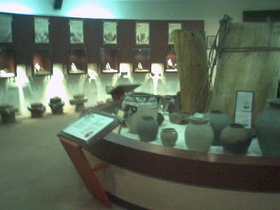 Foreground: kimchi fermenting pots; background: explanation of kimchi-making steps
