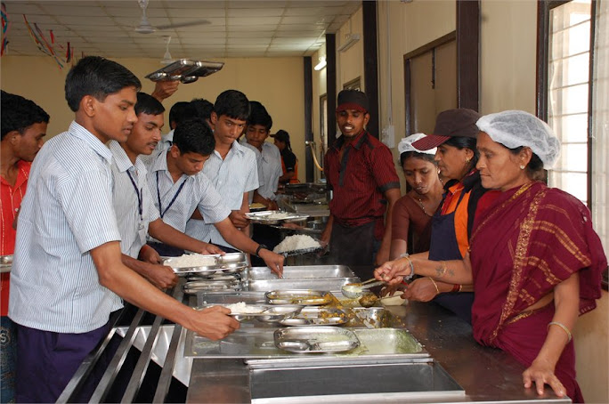 workers serving to students at mess