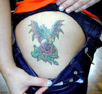Dragão e rosa tatuados na coxa superior
