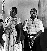 Photo of Ella Fitzgerald and Louis Armstrong singing together, links to CD titled Ella & Louis