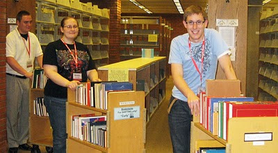 photo of student assistants with loaded book carts