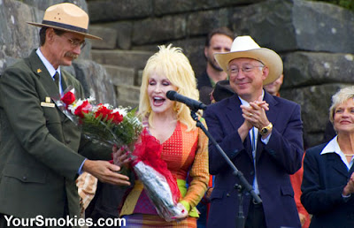 Dolly Parton receives a bouquet of flowers from Dale Ditmanson superintendent of the Great Smoky Mountains national park while Secretary of the Department of the Interior Ken Salazar and NC Governor Bev Perdue look on