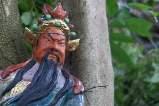 Image of a ceramic protective deity in the forest of Hong Kong