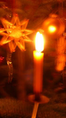 Blurry image of a candle burning on a Christmas tree.