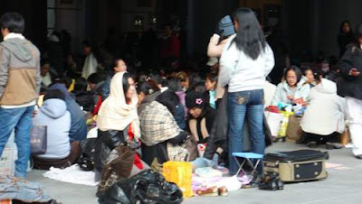 Image of Filipino domestic workers setting up for the day, in numerous huddled groups, under HSBC's flagship banking complex in Hong Kong in the outdoor foyer. It is much darker, but this space stretches out to the street on the other side of the block, and it is full of Filipinos.