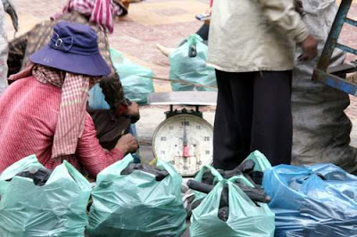Image of a Cambodian man passing charcoal, carbonized wood, on to his helpers to sort and repackage in smaller sacks.