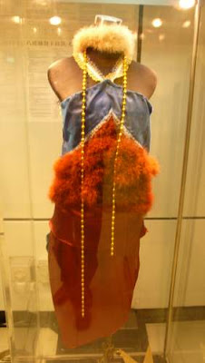 Image of a a designer dress found in an MTR exhibit on Hong Kong fashion in the MTR (subway system). Name of the dress: Orphaned bird, difficult cry (mandarin ducks). Designer: So Hoi-yi. Materials: Cloth, feather, lace, ribbon.