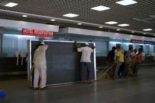 Image of a gang of men hauling a chunk of cast aluminum in Mumbai (Bombay) International Airport.