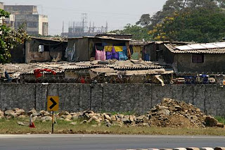 Image of the slums, in the daytime, huddled against the walls of Mumbai's International Airport.